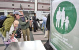 l to r: Amy Gage (cq), daughter Juliana Gage (cq),14 months, and husband Ed Gage (cq) try a green...