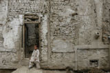 RMX105 - An Afghan boy watches his friends, unseen, playing as he sits near the door of his house...