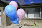 DM0013   Balloons, stuffed animals, flowers and notes cover the front porch of the home where...