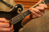 Detail of Brian Mullins playing the mandolin during rehearsal with band mates of the Irish folk...
