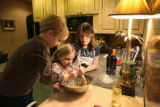 Cian Mesch, 5, left, and his sister Liadh, 7, center, make cookies with Mariel Snyder, 12, right,...