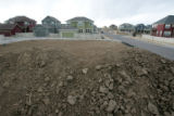 Huge mounds of dirt pile up in a lot next to newly built homes at the Belle Creek subdivision in...