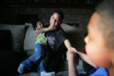 Joshua, 11, (cq) holds his younger sister Lanae, 4, (cq) while Conner, 9, (cq), right, pulls his...