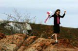 Lexi Hellums (cq), 8, plays on the rocks with the bouquet of her sister Annie Hellums (cq), who is...