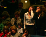 A pair of mourners cry as they stand during a song by the Flobots at the memorial service for...