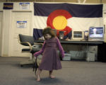 "Grace VanWie, 3, plays with her dinosaur ""Grandpa,"" who she said she was voting for,..."