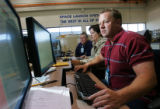 Test Engineer Jerry Hill Jr., sits at the test conductor console with System Engineer, Pat Stroh,...