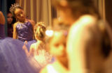(DENVER, Colo., December 16 2004.)  Manuel Nunez, 11, looks from behind the curtain as the...