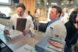 Thomas Keller (cq) autographs a book for student Evan Moore (cq)   at Johnson & Wales...