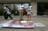 (PG0248) Pedestrians react to PETA intern Cassandra Callaghan poses as a corpse during a...