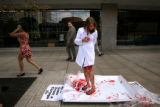 (PG0295) PETA intern Cassandra Callaghan wraps herself in a shirt after posing as a corpse during...