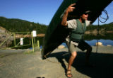 Jeroen Van Wolferen (cq), of Coal Creek Canyon, lifts his canoe before going boating with his son...
