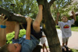 MJM993  Riley Barnhill, 6, swings from a tree as Christian Roby (cq), 9, jumps for a branch Friday...