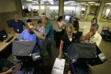 Several Denver Elections Divison personnel test the voting system that will be used for the August...