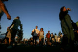 Festival goers walk around the merchandise and food vendor area as the sun sets during Mile High...