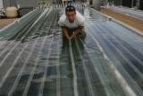 Jon Seibert, 19, (cq) an intern for Solix Biofuels, from San Diego cleans the algae containment...