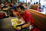 Michael Blatchford, 22, (cq) cyclist, eats a smothered burrito inside the cafeteria at the United...