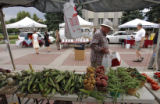 188  Shoppers pass a table filled with vegetables from Miller Farms during the weekly Civic Center...