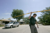 Deputy Grey La Certe lifts up police tape after examining a car that was allegedly stolen and...
