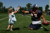 Mike Leach, tight end (cq) gives a high five to quarterback Patrick Ramsey's (cq) daughter, Ellen,...