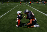 Mike Leach, tight end (cq) waits for his son Ryan, 2, to tackle him after the Denver Broncos...