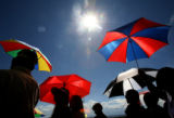 Members of the Laos, Cambodia and Vietnamese communities shield themselves from the sun, as they...