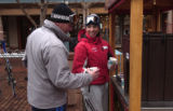 (Aspen, Colo., December 29, 2004) Jamie Britt, right, hands a cup of coffee to Bryan Peterson by...