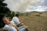 Katie Elmont, 20, and Josh Alley, 23, sit atop a shed to watch a wilfire said to be started by...