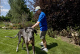 Sam Johnson, (cq) President and Scoop Master of Pet Scoop talks to Duke (cq), a great dane, while...