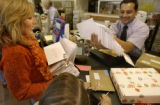 (Denver, Colo., December 20, 2004)    Kim Bolt, of Cherry Hills Village, left, gives a stack of...