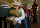 (Denver, Colo., December 20, 2004)    Erin Gust, 9, of Denver, balances 2 boxes and some Christmas...