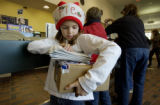 (Denver, Colo., December 20, 2004)    Erin Gust, 9, of Denver, holds a box and some Christmas...