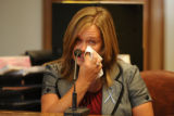 Amy Domanski, a teacher's aide at Holm Elementary School, cries while giving testimony during the...