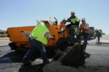 Forman Hector Dominguoz (cq), right front, works with crew from Metro Paving, while putting down...