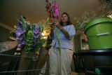 Joan Kinney at the her hometakes her newly cut flowers into her air conditioned kitchen and...