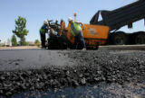 A crew from Metro Paving works on putting down asphalt on Potomack St., Thursday morning, July 31,...