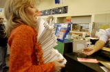 (Denver, Colo., December 20, 2004)    Kim Bolt, of Cherry Hills Village, carries a stack of 200...