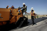 Joel Florez, left, drives a paver while forman Hector Dominguoz guides the edge, Metro Paving,...