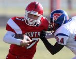 PHOTO BY CHRISTOPHER TOMLINSON--Montrose QB Kirk English getting pulled down by the D from...