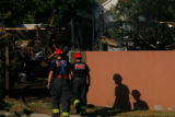 3676  Investigators with West Metro Fire and Rescue survey the scene of a fire in the Roxborough...