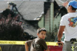 Ben Arellano, 38, right, and his son, Nick, 9, watch workers on the roof of a house that caught...
