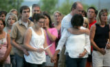Friends and family of the three victims of a house fire early Sunday morning gather outside...