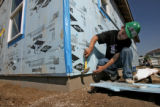 Bachir Belmehdi (cq) works on hammering insulation on the side of his Habitat for Humanity home,...