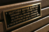 DM2359  A metal plaque memorializing Matthew Shepard shines in the afternoon sun on a bench in...