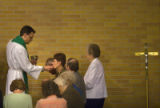 (070)  Rev. Charles W. Westby offers a communion to Barb Clark, 61, of Thornton, while other...