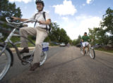 (016)  A Pedal to Properties real estate agent Chris Cullen hands a bike helmet to one of his...