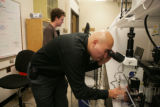 Student researcher Dennis Gardner, 21 (cq) looks in a microscope as Chris Twombly, 20 (cq) stands...