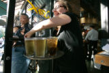 0325 Jen Burt, a server at Jax Fishhouse, 1539 17th St., delivers drinks to a packed patio for...
