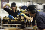 Bottles are examined for fullness and correct labeling during bottling of AC Golden Brewing's...