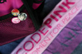 Buttons decorate Alicia Forrest's pink backpack beside a few CodePink clothing pieces.